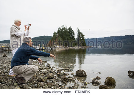 Senior couple skimming stones videoing cell phone lake - Stock Photo