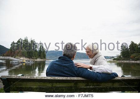 Senior couple laughing on bench overlooking lake - Stock Photo