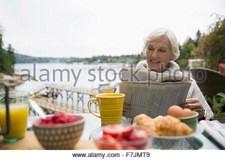 Senior woman reading newspaper breakfast patio lakeside - Stock Photo