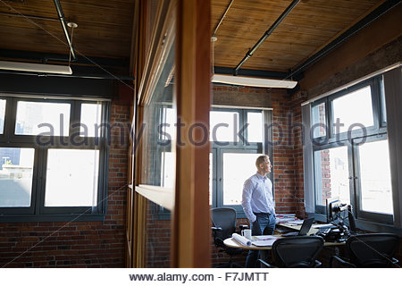 Pensive businessman looking out office window - Stock Photo