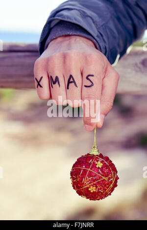 closeup of a young caucasian man with the word xmas written in the knuckles of his hand holding a red christmas - Stock Photo