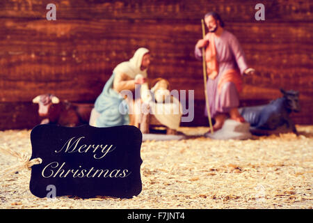 a black label with the text merry christmas and the holy family in a rustic nativity scene - Stock Photo