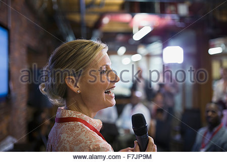 Close up businesswoman with microphone speaking at conference - Stock Photo