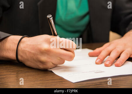 Hands of man sitting working in an office signing a sheet of paper or document with a pen, on dark desktop - Stock Photo