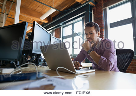 Focused businessman working at laptop in office - Stock Photo