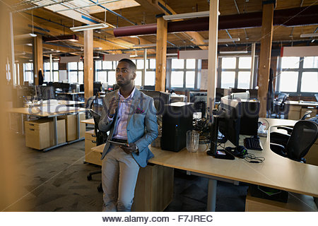 Pensive businessman brainstorming in open office - Stock Photo