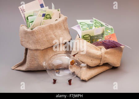 Two money bag with euro and glass piggy bank on gray - Stock Photo