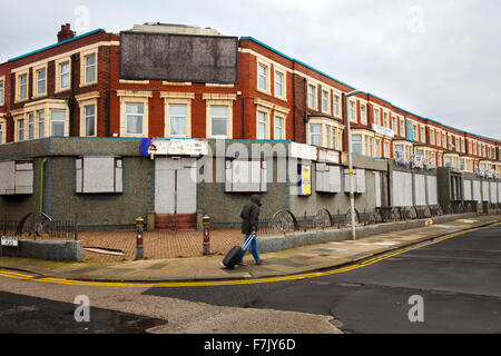 Man with Suitcase passing Seafront Hotels in permanent decline. These were the bed and breakfast hotels that fueled - Stock Photo