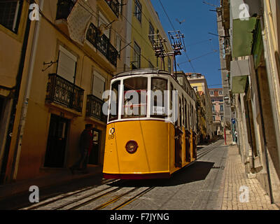 Yellow tram in the narrow streets of lisbon - Stock Photo