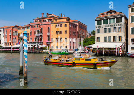 Venice, Italy.  A DHL courier boat, laden with packets for delivery, motors down the Grand Canal. - Stock Photo