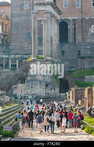 Rome, Italy.  Visitors in the Roman Forum walking towards the ruins of the Temple of Saturn. - Stock Photo