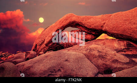 Purple sunset and rising moon over arch in Joshua Tree National Park, California, USA. - Stock Photo