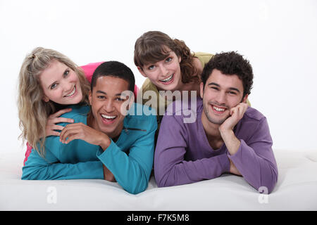 Two couples lying in bed. - Stock Photo