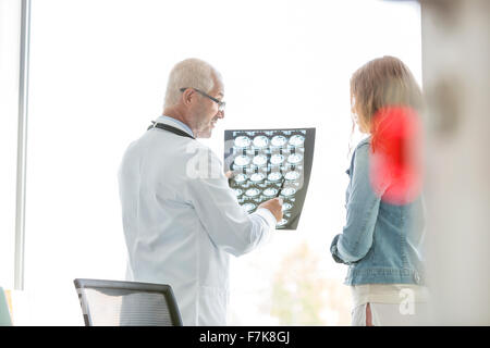 Doctor reviewing x-rays with patient in doctor's office - Stock Photo