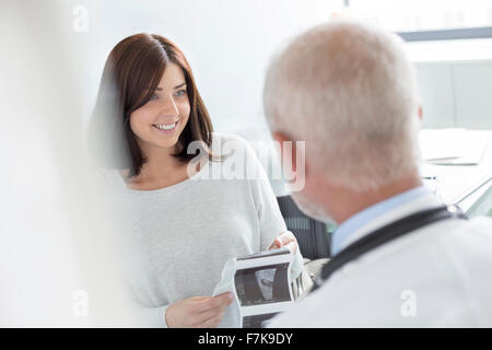 Doctor and patient looking at ultrasound x-rays in doctor's office - Stock Photo