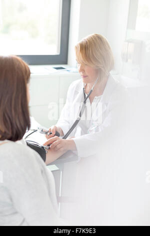 Doctor checking patient's blood pressure in examination room - Stock Photo