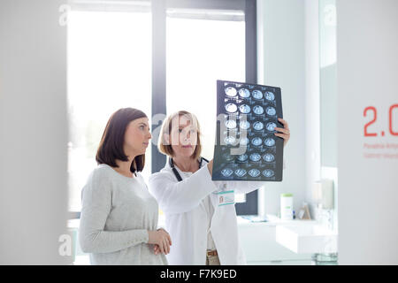 Serious doctor and patient reviewing x-rays in examination room - Stock Photo