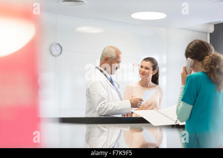 Doctor and patient discussing medical record at nurses station - Stock Photo