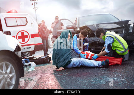 Rescue workers preparing vacuum leg splint on car accident victim in road - Stock Photo