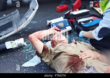 Car accident victim laying in road - Stock Photo
