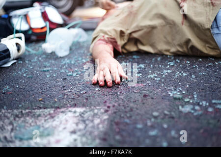 Bloody hand of car accident victim in road among shattered glass - Stock Photo