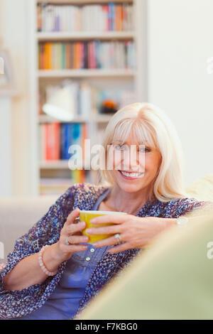 Portrait smiling senior woman drinking coffee on sofa - Stock Photo