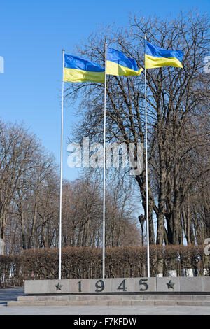 Three Ukrainian flag on flagpoles against the bright spring sky. - Stock Photo