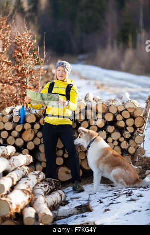Woman camping on hiking in forest and reading map with dog. Recreation and healthy lifestyle outdoors in nature. - Stock Photo