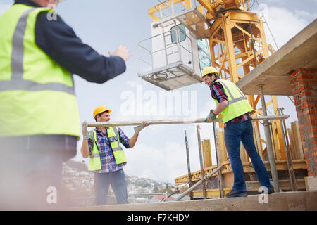 Construction workers lifting metal pole below crane at construction site - Stock Photo