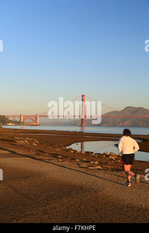 Male runner (on Crissy Field) and Golden Gate Bridge, San Francisco, California USA - Stock Photo