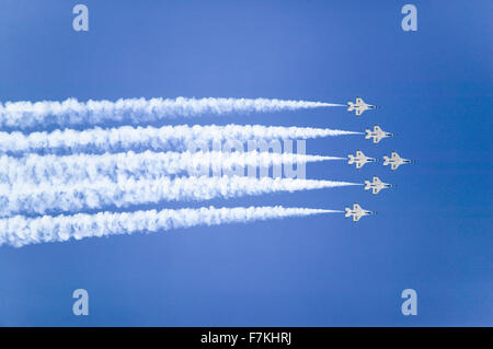 Six US Air Force F-16C Fighting Falcons, known as the Thunderbirds, flying in formation with white trailer of smoke - Stock Photo