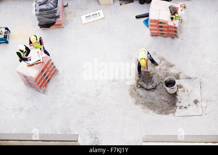 Overhead view of construction workers laying concrete at construction site - Stock Photo