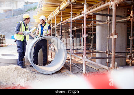 Construction workers talking at construction site - Stock Photo