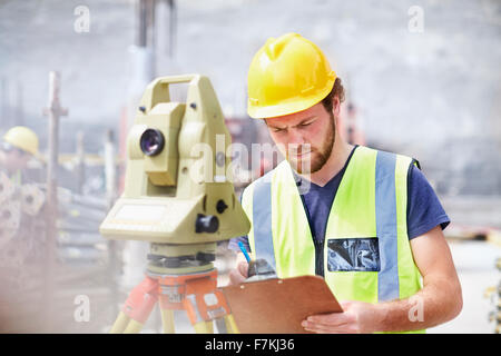 Engineer with clipboard behind theodolite at construction site - Stock Photo