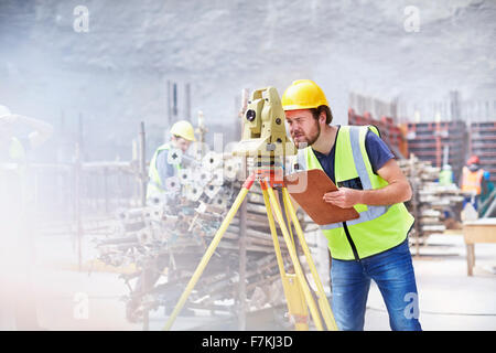Engineer with clipboard using theodolite at construction site - Stock Photo