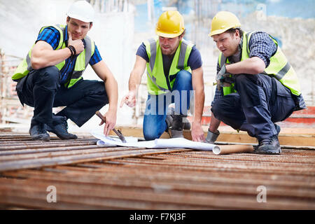 Construction workers and engineer reviewing blueprints at construction site - Stock Photo