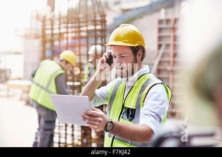 Engineer with digital tablet talking on cell phone at construction site - Stock Photo