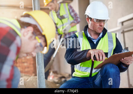 Foreman with clipboard at construction site - Stock Photo