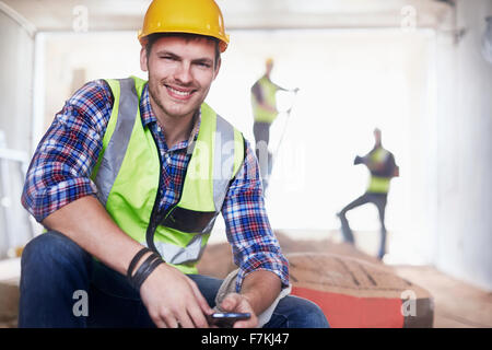 Portrait smiling construction worker with cell phone at construction site - Stock Photo