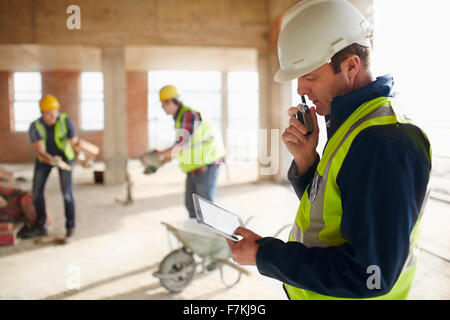Foreman with digital tablet using walkie-talkie at construction site - Stock Photo