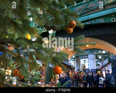 CHRISTMAS TREE Borough Market stalls viewed through Christmas tree and lights Southwark London - Stock Photo