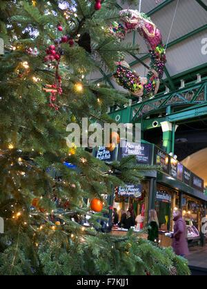 Borough Market stalls viewed through Christmas tree and lights Southwark London - Stock Photo