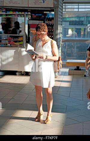 Woman reads book as she waits for train in Boston, Ma., USA - Stock Photo