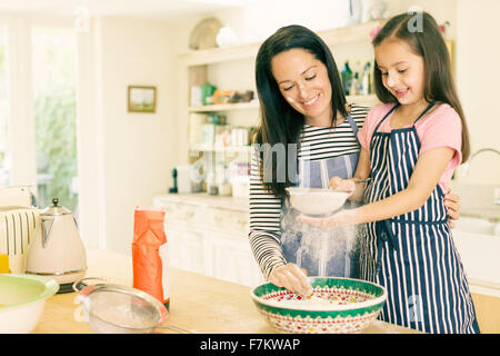 Mother and daughter baking sifting flour in kitchen - Stock Photo