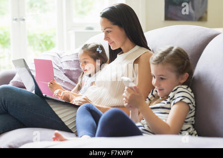 Mother and daughters with laptop, cell phone and digital tablet on sofa - Stock Photo