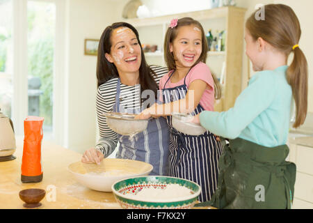 Laughing mother and daughters baking with flour on faces in kitchen - Stock Photo