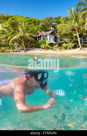 Tropical Ko Samet Island, underwater view of snorkeling woman and fish, Thailand, Asia - Stock Photo