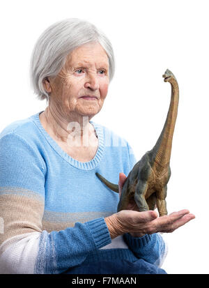 Portrait of a senior woman holding a toy dinosaur over white background, aging concept, humorous aspect - Stock Photo