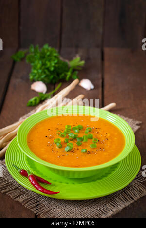 Delicious cream of pumpkin soup in green bowl on old wooden table - Stock Photo