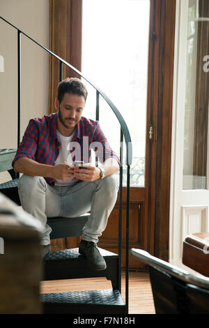 Man sitting on staircase using smartphone - Stock Photo